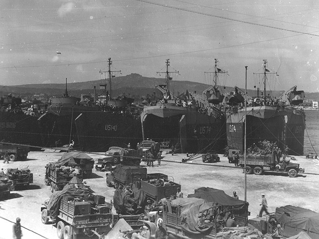 LST's line Naples' docks loading elements of VI Corps' main infantry divisions, the Third, 36th and 45th, for Operation Dragoon. All three divisions had previously embarked from Naples for Anzio. The trucks are queued to back through the massive doors of the ship.