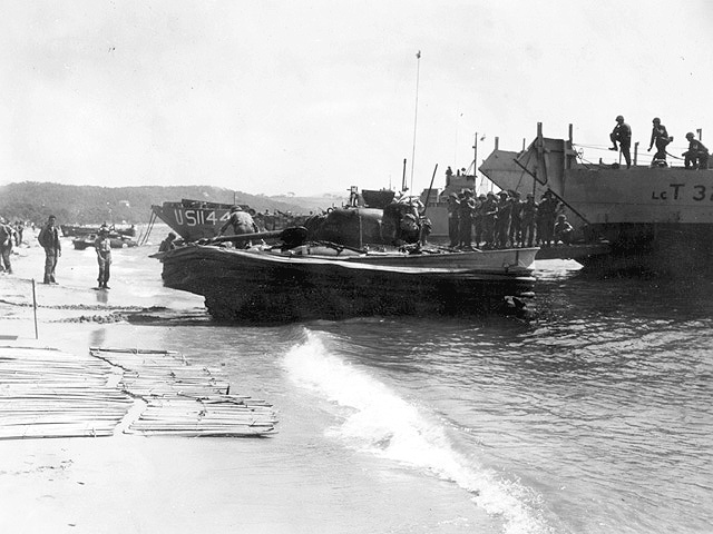 One of four DD (Duplex Drive) tanks from the 756th Tank Battalion attached to the Third Division exits the water at Red Beach. A canvas flotation apron was attached to a welded boat-shaped platform on a Sherman tank to make the DD buoyant with a 4-knot water speed from two aft propellers.